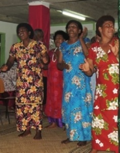 The village ladies dance a welcome for us