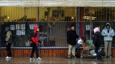 A group of homeless and poor seek shelter from the rain outside a store in the Downtown Eastside area of Vancouver on February 11, 2010. Canada is spending over two billion dollars on the Winter Olympics but just steps away from the venue for the opening ceremony sits one of the country's most notorious slums where drug addiction and prostitution are rife. The scenes of homelessness and the squalor of Downtown Eastside are not the images Olympic organizers want visitors to leave with. But the neighbourhood's close proximity to BC Place Stadium where the Olympic cauldron will be lit on Feb.12, will make it hard for visitors to miss. AFP PHOTO/Mark RALSTON (Photo credit should read MARK RALSTON/AFP/Getty Images)